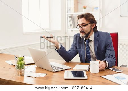 Stressed Businessman With Laptop In Modern White Office Interior, Indignantly Looking At Computer Sc