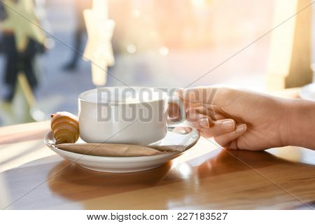 Woman holding cup of aromatic coffee at table. Tasty breakfast