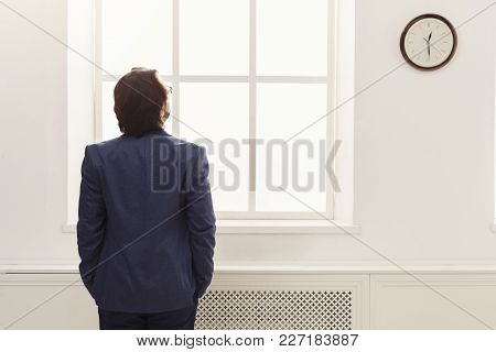 Businessman Looking At Clock In Office, Ready Go Home, Back View, Copy Space
