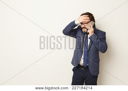 Stressed Businessman Talking On Phone And Touching His Forehead. Job Problems Concept, Copy Space, W