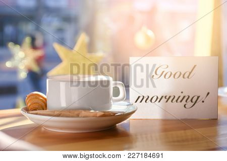 Cup of aromatic coffee and card with words