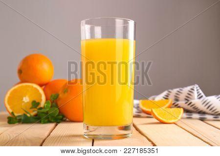 Glass of fresh orange juice on wooden table