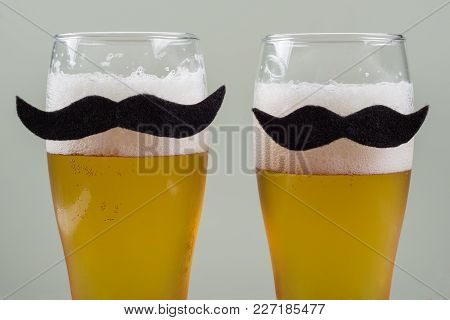 Two Glasses With Beer And A Symbolic Mustache. Background - Olive Wall.