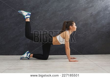 Fitness Woman Warmup Stretching Training At Grey Background Indoors. Young Slim Girl Making Aerobics