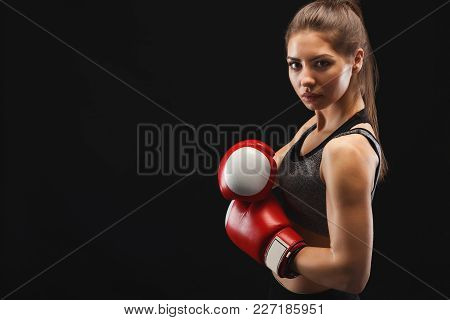 Side View Of A Gorgeous Young Woman With Boxing Gloves, Ready To Fight, Copy Space. Studio Shot On B