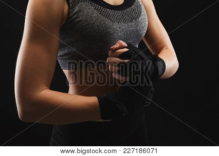 Athletic Female Boxer Wrapping Hands With Boxing Tape Before Fight. Female Fitness Model With Muscul