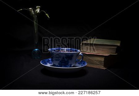 Nostalgic Still Life Photograph Of Antique Cup And Saucer Of Tea With Old Hardback Books And Bud Vas