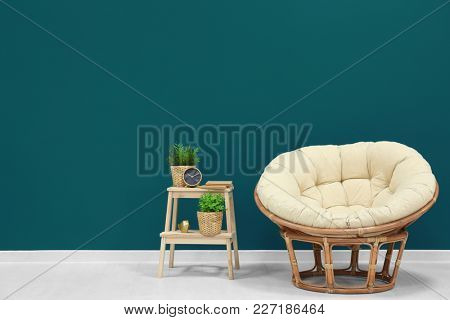 Trendy living room interior with comfortable armchair against shaded spruce wall