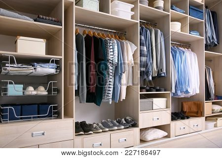 Big wardrobe with male clothes for dressing room