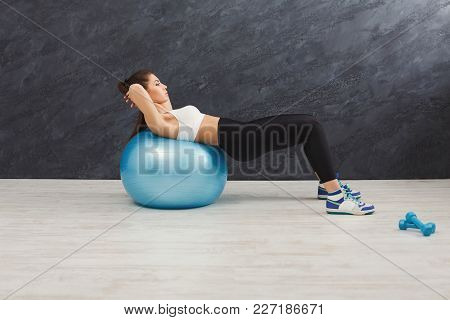 Fitness Woman Working On Her Abs With Fitness Ball At Gym. Young Slim Girl Making Aerobics Exercise.