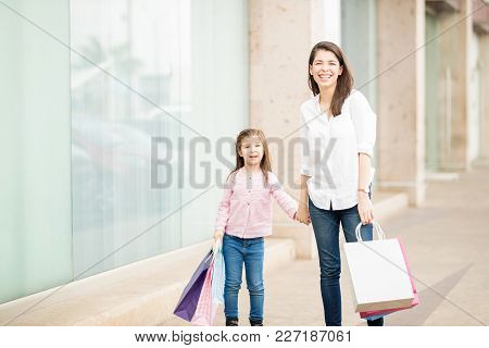 Portrait Of Cute Latin Mother And Daughter Walking Around A Shopping Center Carrying Shopping Bags A