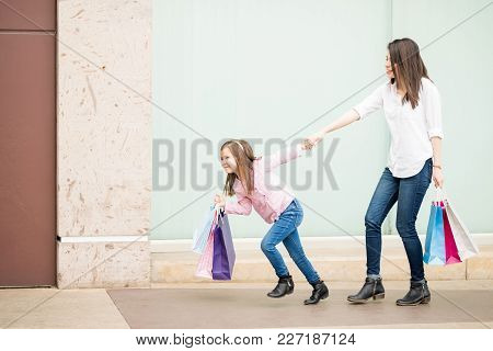 Full Length Of A Cute Little Latin Girl Pulling Her Shopaholic Mother Out Off A Shopping Mall