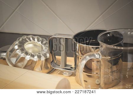 Kitchen Utensil, Wooden Rolling Pin With Glass Measuring Cup And Cake Molds On A Wooden Cutting Boar