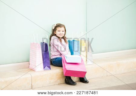 Portrait Of A Cute Little Girl Sitting At Storefront Of A Mall With Shopping Bags