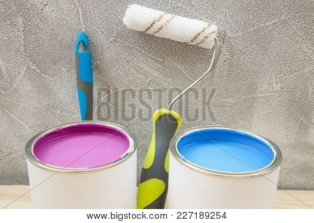 Tin Cans Of Pink And Blue Oil Paint, A Roller Paint And A Brush Against A Light Concrete Wall