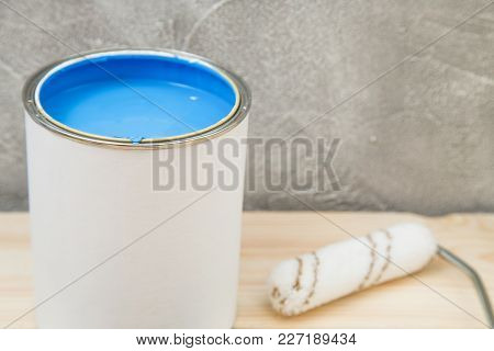 Tin Can Of Blue Oil Paint And A Roller Paint On A Light Uncolored Wooden Surface Against A Light Con