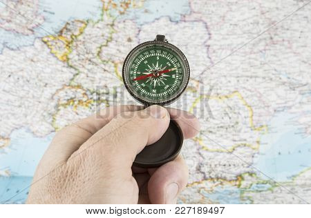Compass In The Hand With Map In The Background