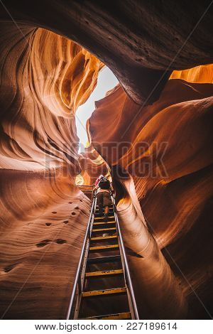 Amazing Sandstone Formations With Hikers Ascending A Steep Ladder In Famous Antelope Canyon On A Sun