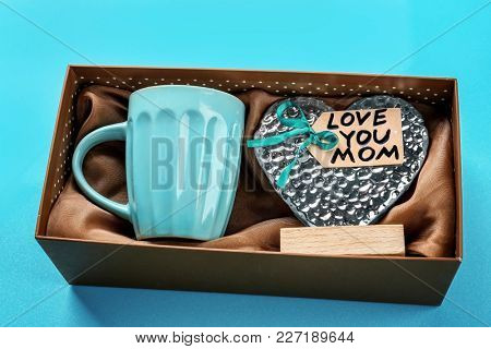 Gift box with cup and heart figure on color background. Mother's day celebration