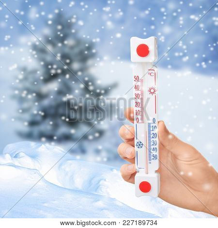 Woman with thermometer registering temperature below zero outdoor