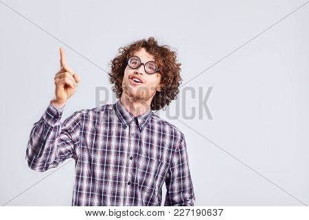 Curly Nerd Man In Glasses With A Stupid Kind Of Funny Emotion On A Gray Background.