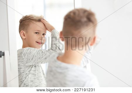 Cute little boy looking at himself in mirror indoors