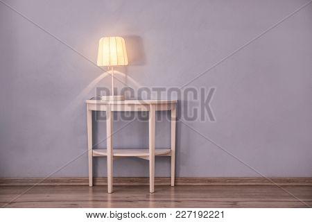 Stylish table lamp near color wall