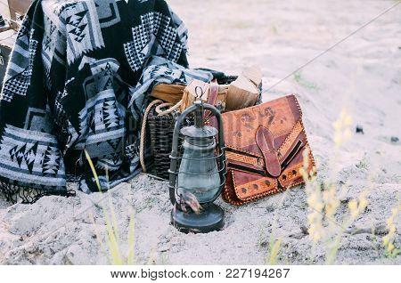 Old Kerosene Lamp Near Boho Vintage Bag, Basket With Firewood And Hippie Blanket