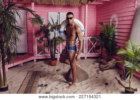 Sexy African American Man In Shorts Standing On The Beach And Holding A Life Buoy.