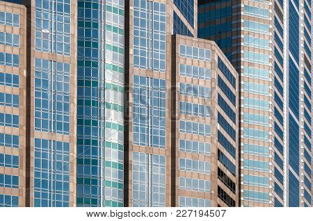 Closeup To Detail Of Dense Buildings In Business District Area Showing Multiple Color Of Glass Windo