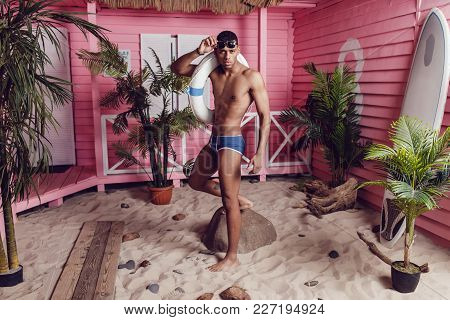 Sexy African American Man In Shorts Standing On The Sand And Holding A Life Buoy.