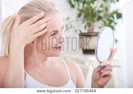 Forty Years Old Woman Looking At Wrinkles In Mirror. Plastic Surgery And Collagen Injections. Makeup