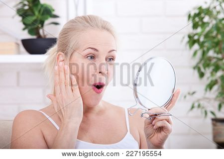 Middle Aged Woman Looking At Wrinkles In Mirror. Plastic Surgery And Collagen Injections. Makeup. Ma