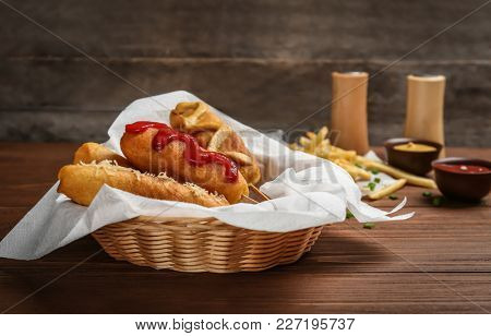 Tasty corn dogs with sauces in basket