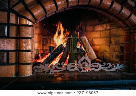 Cozy Flaming Fire In A Stone Fireplace With Red Lights