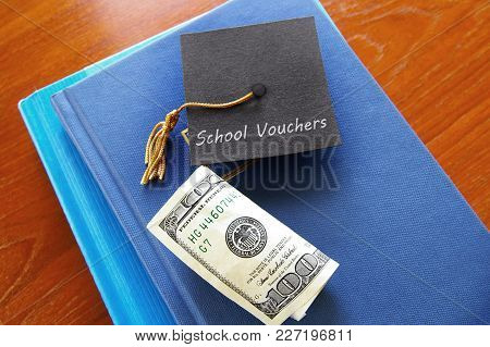 School Vouchers Message On A Small Graduation Cap, With Books And Money