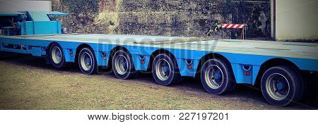 Very Long Blue Truck With Six Axles Of Wheels For Exceptional Transport With Vintage Effect