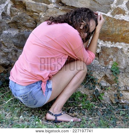 Abused And Frightened Woman Sitting In The Corner Of A Derelict Building.