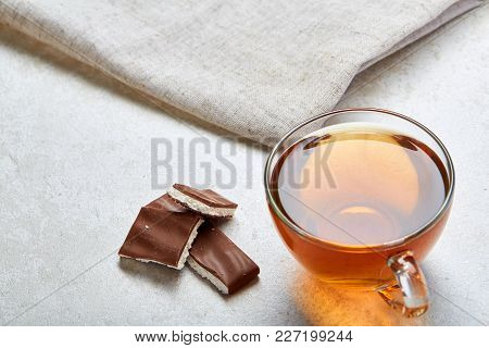 Some Black Or Herbal Tea In Transparent Cup With Tasty Chocolate On Light Grey Burlap Cotton Napkin