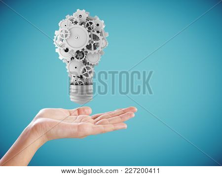 Hand Holding Abstract Gear Lamp On Blue Background. Teamwork And Mechanics Concept. 3d Rendering