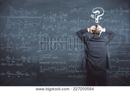 Back View Of Stressed Businessman Standing On Chalkboard Background With Mathematical Formulas. Scie