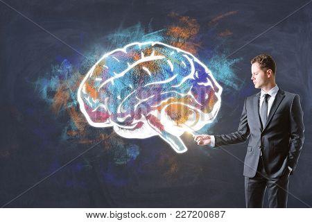 Handsome Caucasian Businessman Drawing Creative Brain Sketch On Chalkboard Wall Background. Brain St