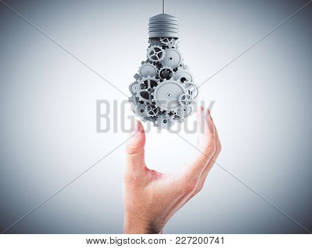 Hand Holding Abstract Gear Lamp On Grey Background. Teamwork And Engineering Concept. 3d Rendering