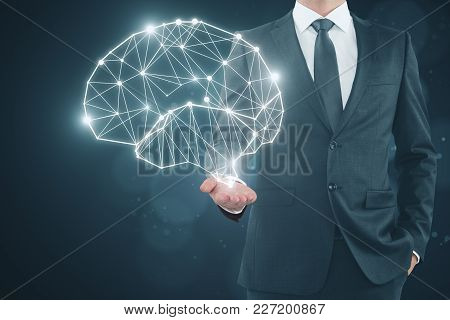 Businessman Holding Glowing Polygonal Brain On Dark Background. Artificial Intelligence And Future C