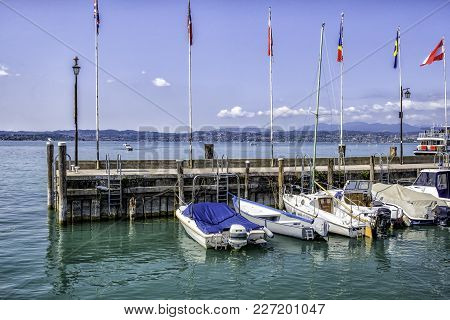 Pier On The Lake Guard With Boats On A Bright Sunny Day. Italy.
