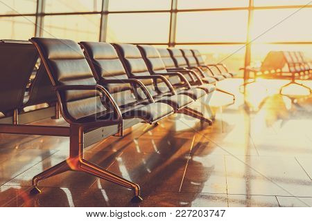 Empty Seats In The Departure Lounge At The Airport In The Sunset.