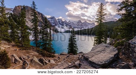 Moraine Lake In Banff National Park, Canada At Sunset Including Mountain Peaks, Clouds, Forest, Tree