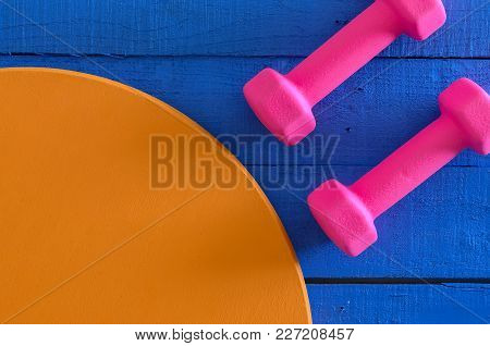 Dumbbells On Wooden Background With Copy Space. Saturated Colors (blue, Orange, Pink). Sport Equipme