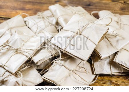 Close-up Many Gifts Wrapped Kraft Paper On Wooden Background.