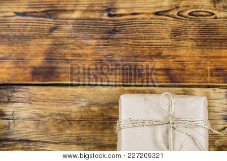 Close-up Quater Gift Wrapped Kraft Paper On Wooden Background. Left On Photo
